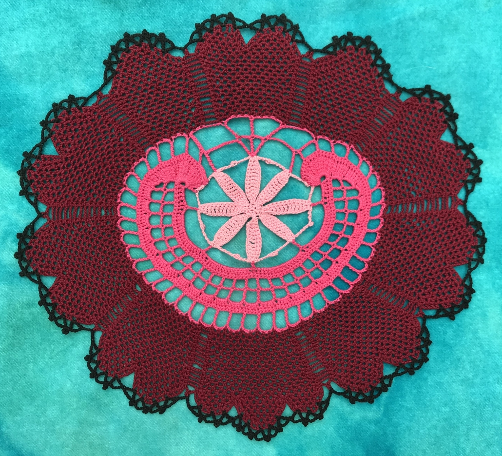 Image of the American Rose doily, crocheted in red, pink, and black yarn