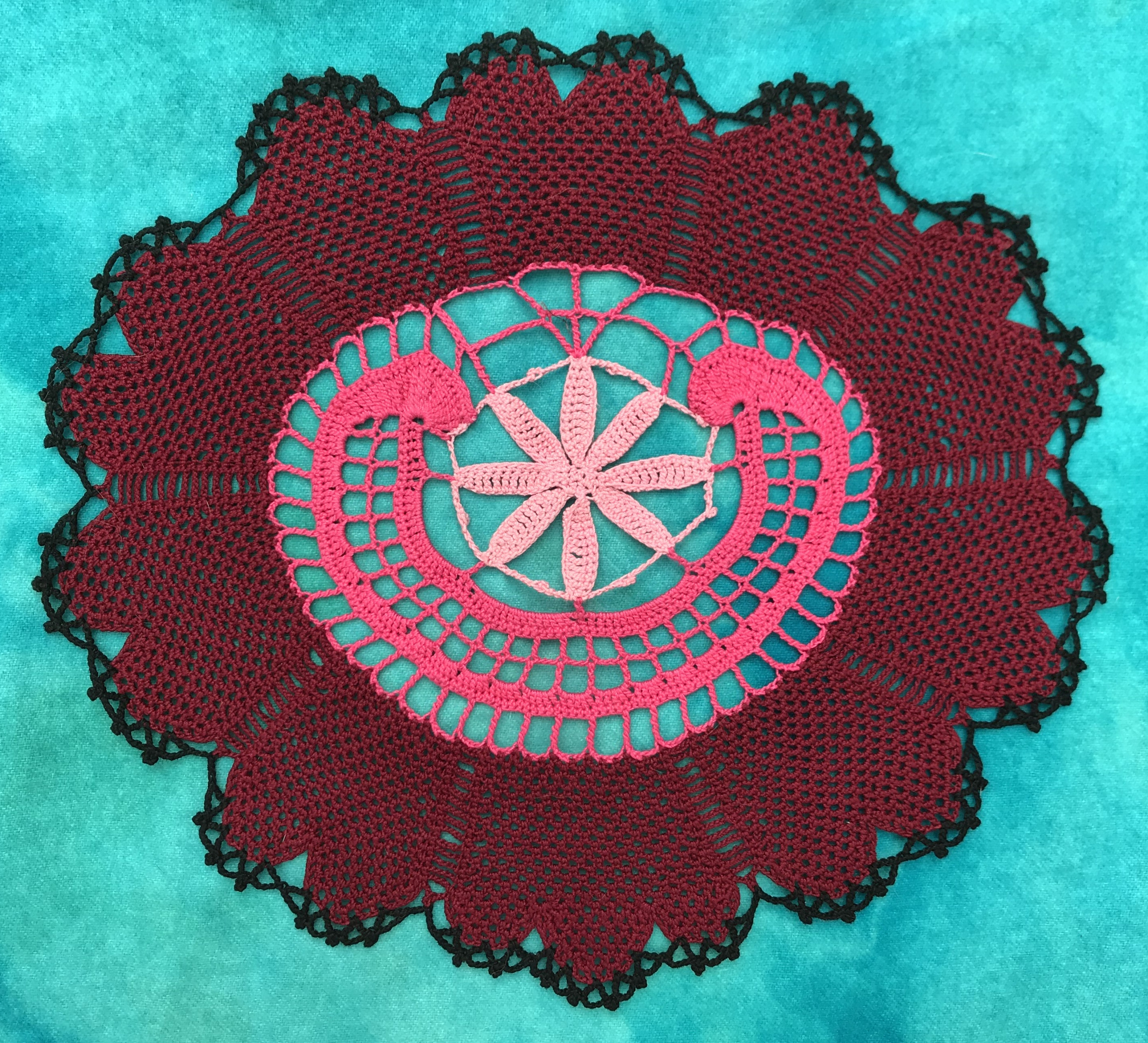 Image of the American Beauty Rose crocheted doily, in red and pink cotton on a teal background