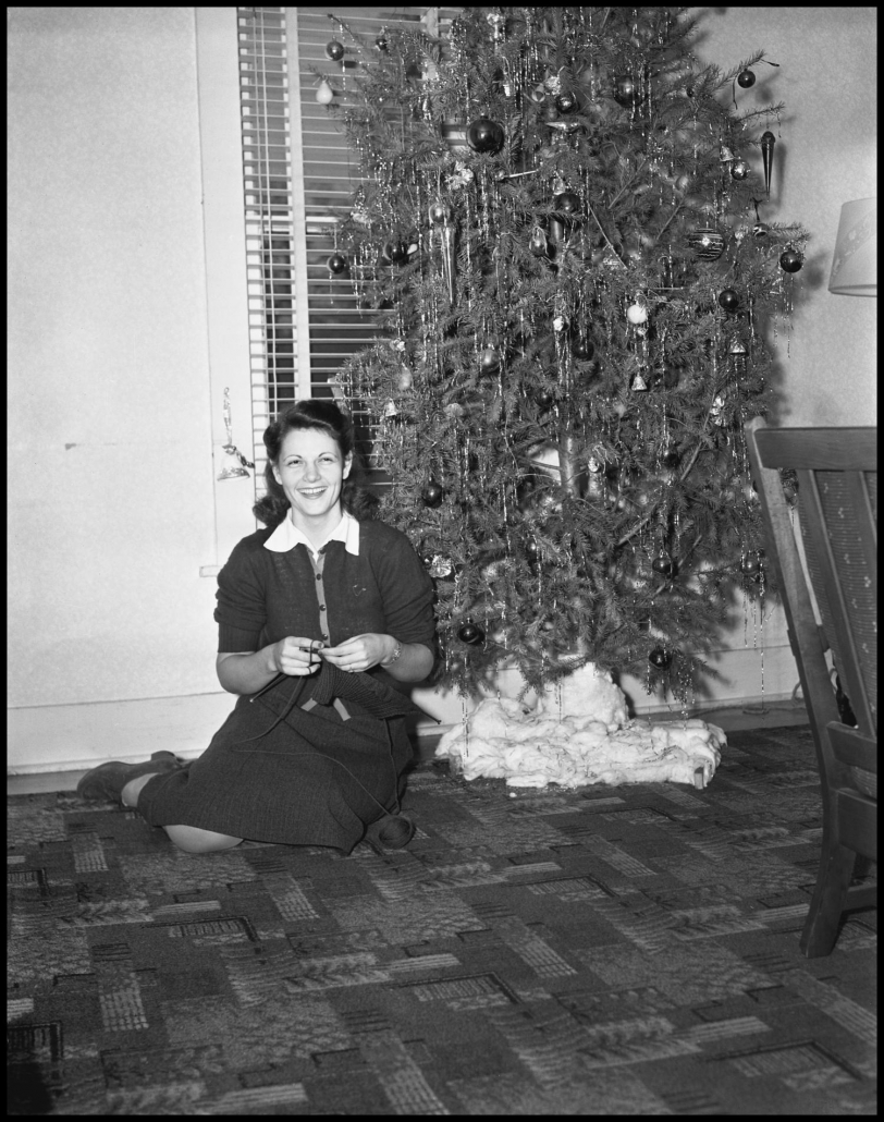 A woman pictured sitting under a Christmas tree, knitting a sleeveless sweater for a soldier. It is in the collection of the University of North Texas Special Collections, and available through CKC's Museum and Archives collection