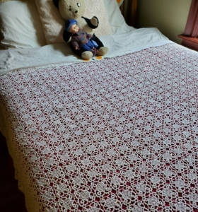 coverlet of assembled lacy crocheted squares on a large bed with folded over top sheet that is embroidered with a poppy motif, with a stuffed panda bear and a baby doll lying on the pillows